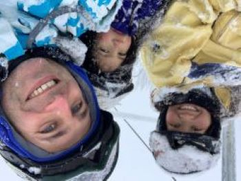 family of three on a chairlift in the snow
